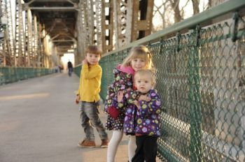 Three young walkers try out the Meridian Bridge on its reopening day as a footbridge.
